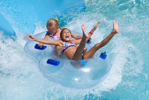 girls sliding down a waterslide on a tube laughing